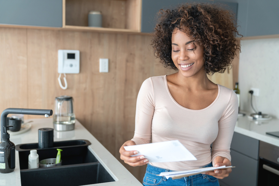 Portrait of an African American woman at home checking her mail and looking very happy – lifestyle concepts