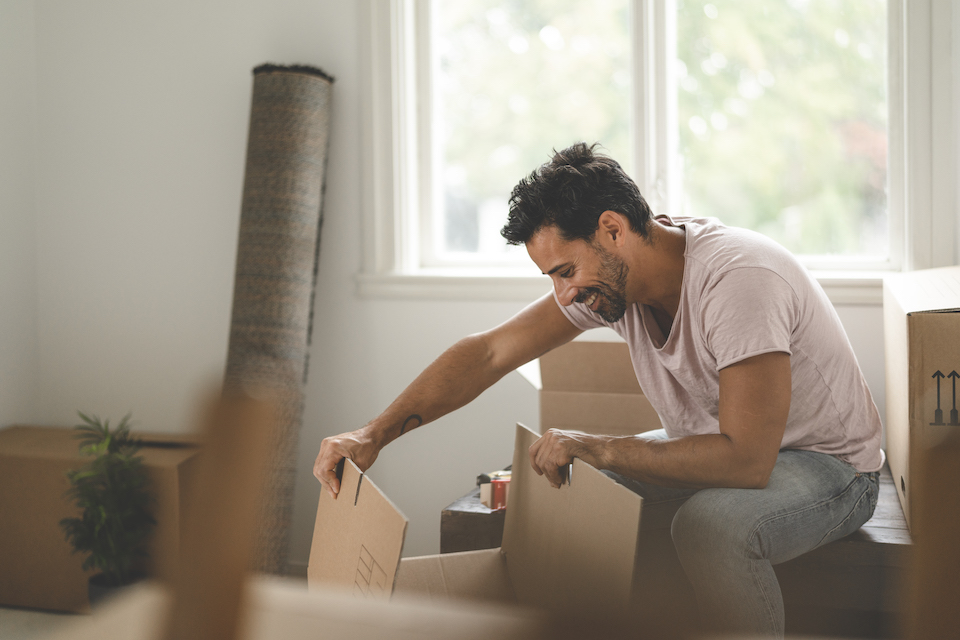 A mature hispanic man is packing and unpacking as he is moving into a new house.