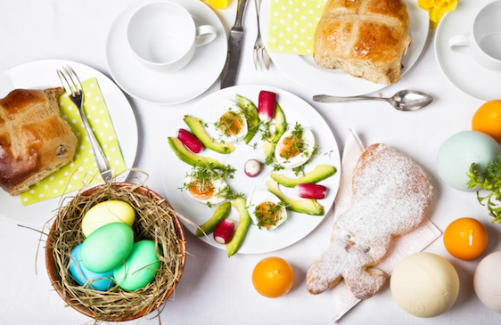 easter brunch table with eggs, cross buns and a baked easter bunny
