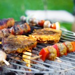 Some vegetable and meat skewer and some pieces of pork meat on a flamy grill in a garden. XXL size image.
