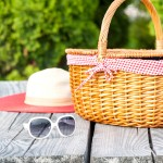 Ready for summer holidays. White sunglasses summer hat and wicker basket on wooden table background. Multicolored vibrant outdoors horizontal image.