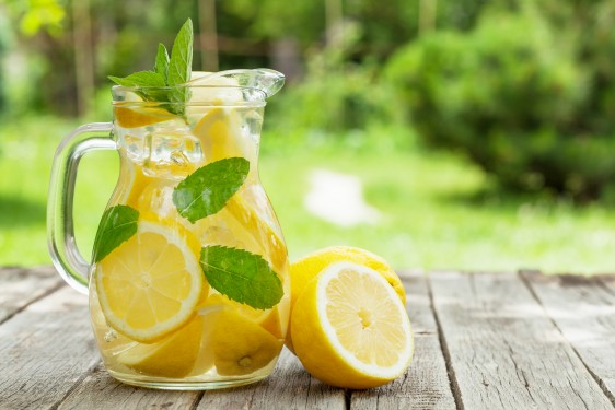 Lemonade pitcher with lemon, mint and ice on garden table. View with copy space