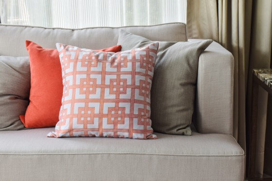 Chinese pattern in orange and deep orange and gray pillows on light gray sofa set