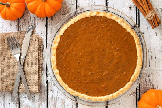 Thanksgiving pumpkin pie in plate, downward view with fork and knife on rustic white wood background