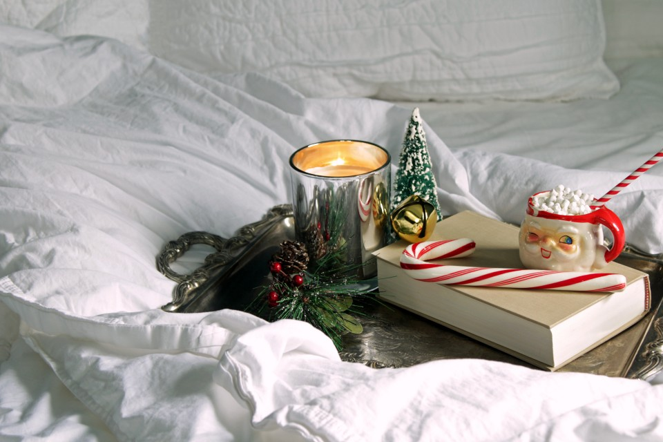 White bedding and silver tray with candle, book and Christmas items. Copy space.