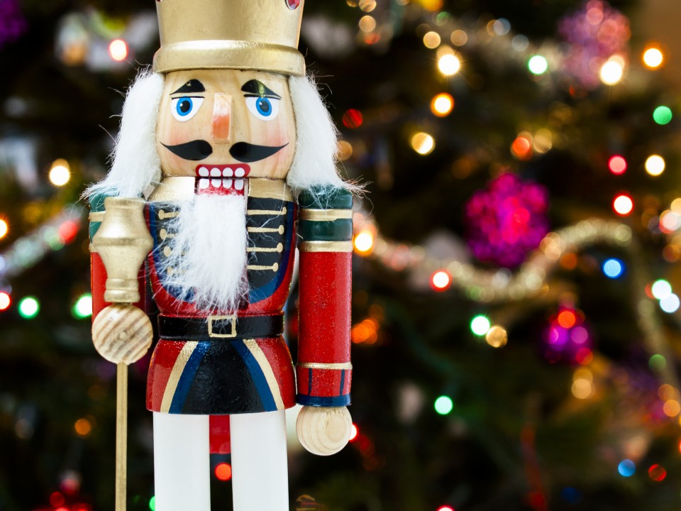 Nutcracker with Christmas tree in the backgound.