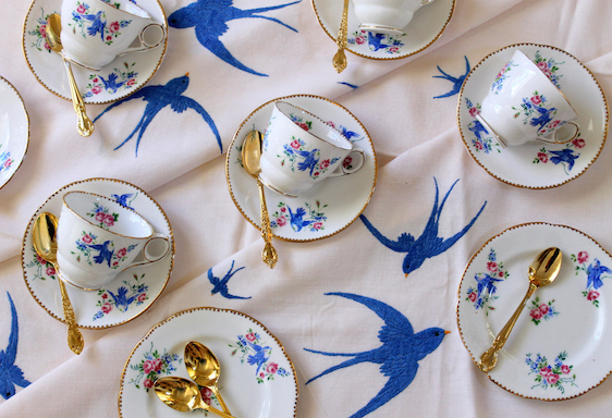 High Tea Party with vintage bluebird teacups and saucers on an embroidered tablecloth - flat lay - overhead view