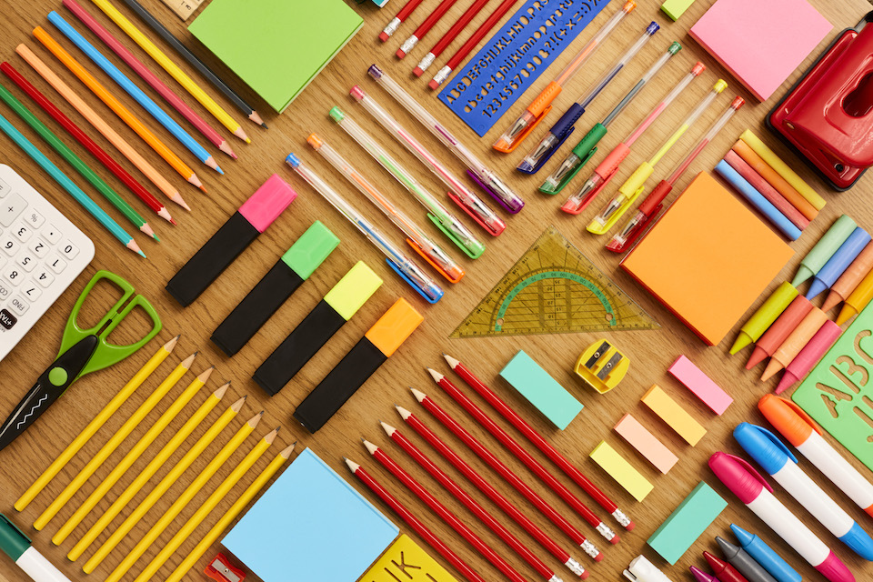 Office and school supplies arranged on wooden table - Knolling