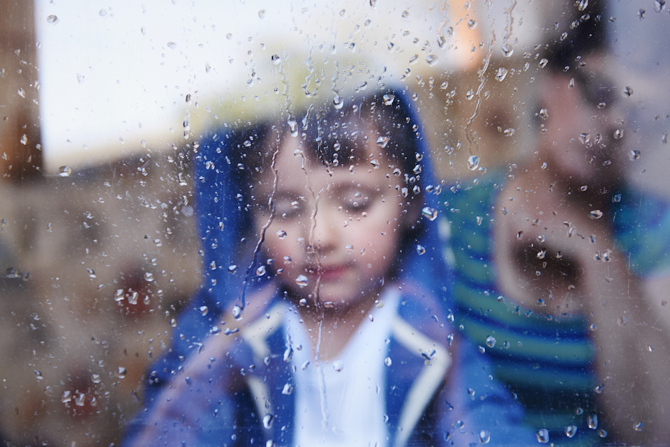 A little boy looking downwards behind a rain-streaked window while his mother sits in the background
