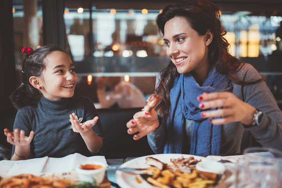 Mother with little daughter eating dinner in restaurant