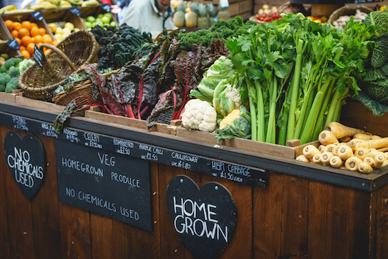 Vegetable stall in farmer market, including celery, parsnips and broccoli.