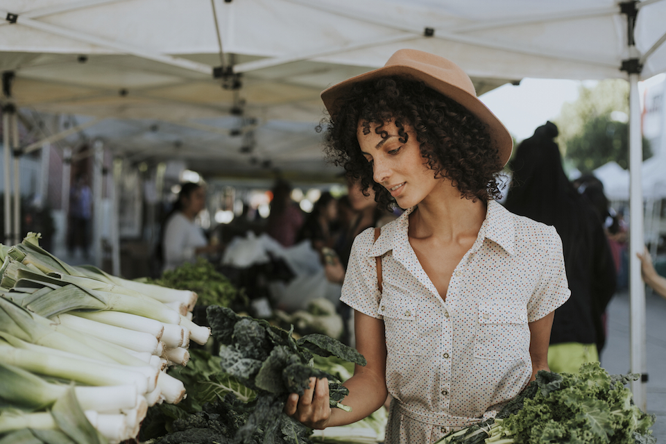 Beautiful woman buying kale at a farmers market