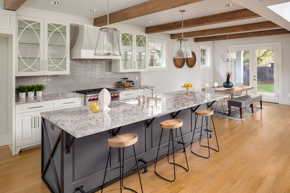 beautiful kitchen with lights off in new luxury home with island, pendant lights, and glass fronted cabinets, and view of dining room