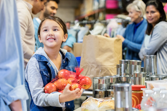 Smiling little girl donates apples to food bank