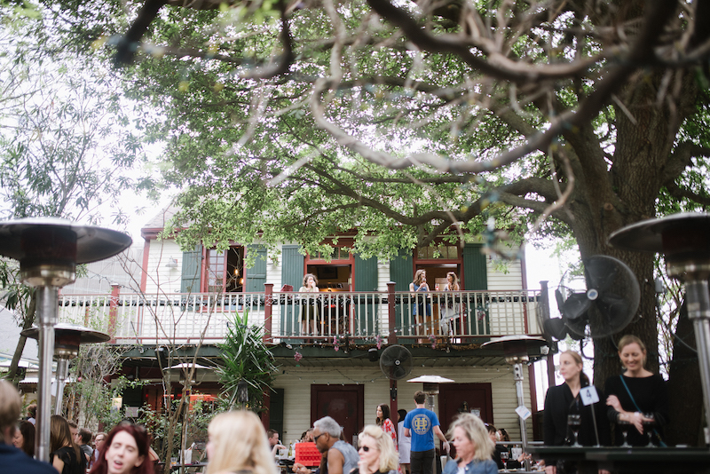This image contains: two females on a balcony drinking wine and a crowd shot of people enjoying the atmosphere at Bacchanal