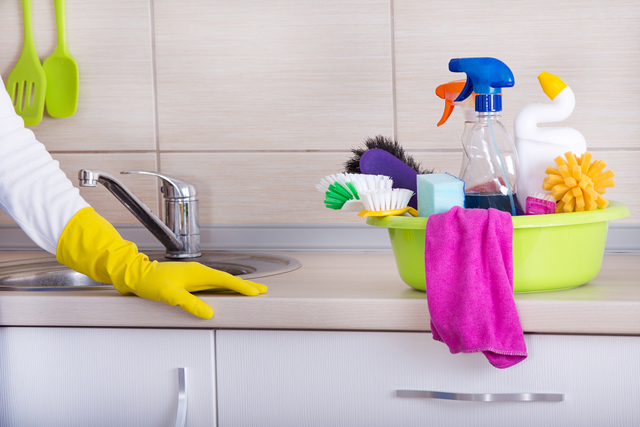Cleaning supplies in washbasin standing on cleaned kitchen countertop. Hand of cleaning lady with rubber glove beside