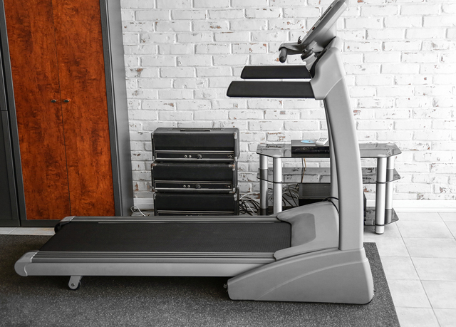 Treadmill in room on brick wall background