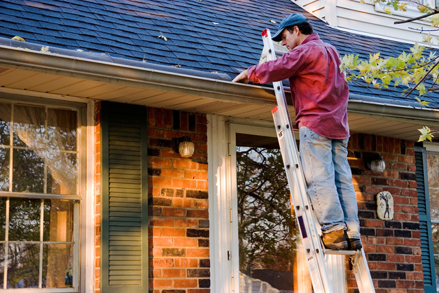 Man Cleaning Gutters on a Ladder Against a Brick House