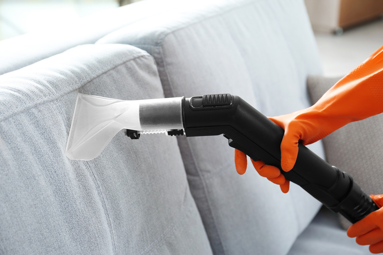 Female hands cleaning couch with vacuum cleaner