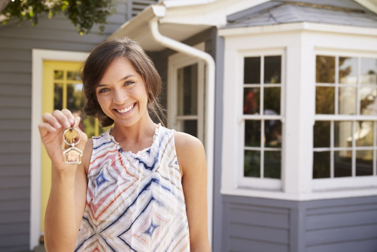 Woman With Keys Standing Outside New Home